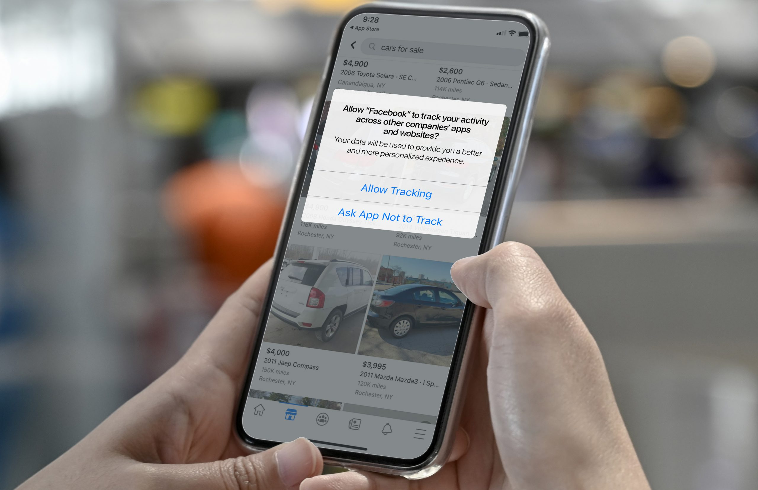 Hands holding smartphone displaying Ad Tracking Transparency prompt in iOS 14